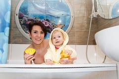 俏丽的妈妈和逗人喜爱的婴孩在卫生间里 库存图片