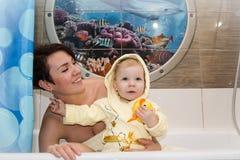 俏丽的妈妈和逗人喜爱的婴孩在卫生间里 免版税库存照片
