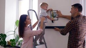 俏丽的孩子在卷尺帮助母亲和父亲下在舱内甲板的修理以后垂悬与图片的架子在墙壁上 股票录像