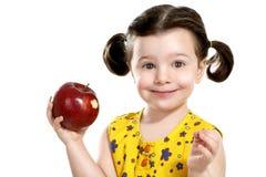 俏丽的孩子在她的手上的拿着一个红色苹果 免版税库存图片