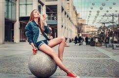 俏丽的少女吹的泡影室外生活方式画象在城市,佩带在行家赃物难看的东西样式都市背景中 免版税库存图片