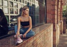 俏丽的少女室外生活方式时尚画象,佩带在行家赃物在都市背景的难看的东西样式   库存照片