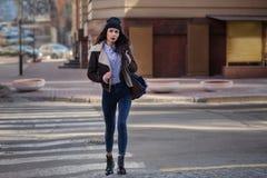 俏丽的少女室外生活方式画象,佩带在行家赃物在都市背景的难看的东西样式 佩带的帽子和牛仔裤 免版税库存图片