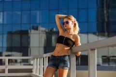 俏丽的少女室外生活方式画象,佩带在行家赃物难看的东西样式和太阳镜在都市背景 r 免版税库存照片
