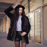 俏丽的少女,在都市背景的佩带的行家赃物难看的东西样式室外生活方式画象  佩带的帽子和牛仔裤 库存照片