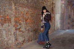 俏丽的少女,在都市背景的佩带的行家赃物难看的东西样式室外生活方式画象  佩带的帽子和牛仔裤与 库存照片