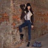 俏丽的少女,在都市背景的佩带的行家赃物难看的东西样式室外生活方式画象  佩带的帽子和牛仔裤与 免版税图库摄影