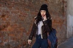 俏丽的少女,在都市背景的佩带的行家赃物难看的东西样式室外生活方式画象  佩带的帽子和牛仔裤与 免版税库存图片