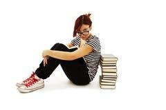 俏丽的少年女孩坐楼层和阅读书 免版税库存图片
