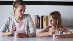 俏丽的年轻互相看母亲和她的女儿,当在家时吃酸奶 股票录像