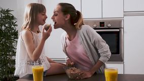 俏丽的年轻享受时间的母亲和她的女儿,当在家时吃早餐在厨房里 股票录像