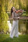 俏丽的年轻女人在公园和微笑,全长画象的弹小提琴 库存照片