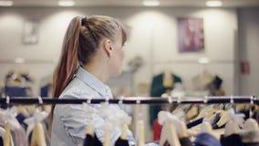 俏丽的年轻女人采取从衣裳机架的一条裙子在服装店和轻易获胜它的 股票录像