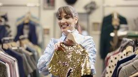 俏丽的年轻女人陈列和尝试在有金黄闪闪发光的一件礼服在服装店 股票录像