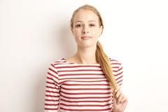 俏丽的年轻女人lookig演播室画象在照相机和微笑的,当站立对被隔绝的白色背景和使用与时 库存图片