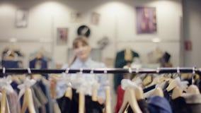 俏丽的年轻女推销员在服装店和放有些裙子走到衣裳机架那里 影视素材