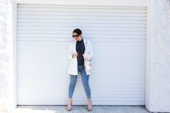 俏丽的年轻摆在白色墙壁背景的时尚肉欲的妇女穿戴在样式牛仔裤成套装备和白色夹克 免版税库存图片