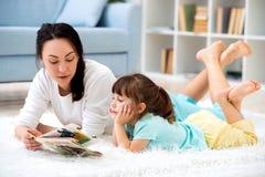 俏丽的年轻母亲看书她的小女儿,说谎在地板上的地毯在家 库存图片
