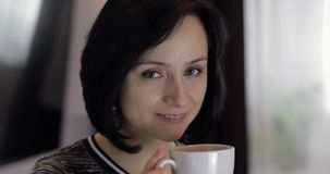 俏丽的年轻深色的妇女微笑的和饮用的咖啡画象从杯子的 股票视频