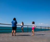 俏丽的年轻西班牙女孩让她的朋友拍照片的她摆在拿着栏杆由海洋,当她年轻时 库存图片