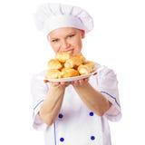 俏丽的微笑的厨师妇女用煮熟的酥皮点心 库存图片