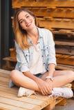 俏丽的微笑的女孩、佩带的摆在木背景的牛仔裤、短裤和衬衣 免版税库存图片