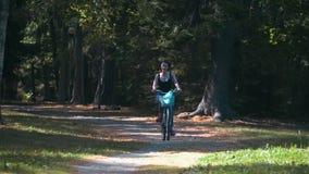 俏丽的微笑的女孩在有绿色树的公园骑自行车在夏天晴天 影视素材
