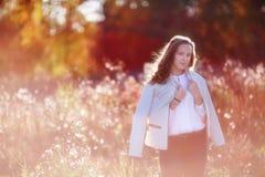 俏丽的微笑的女孩在阳光下 划分为的秋天长凳五颜六色的舍去离开公园结构树 图库摄影