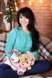 俏丽的微笑的女孩坐在圣诞节的沙发装饰了相互 免版税图库摄影