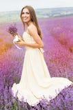 俏丽的微笑的女孩穿礼服在紫色 免版税库存图片