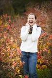 俏丽的微笑的妇女在秋天森林里 免版税库存图片