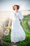 俏丽的微笑的妇女户外与与自然膳食的柳条袋子 免版税库存照片