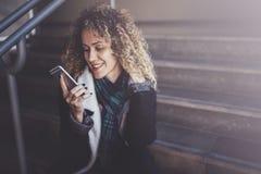 俏丽的微笑的妇女谈话与朋友用她的手机 Bokeh和火光作用对被弄脏的背景 免版税库存照片