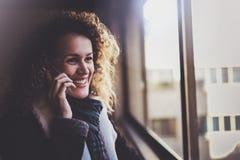 俏丽的微笑的妇女谈话与朋友用她的手机 Bokeh和火光作用对被弄脏的背景 免版税库存图片