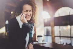 俏丽的微笑的妇女谈话与朋友用她的手机 Bokeh和火光作用对被弄脏的背景 库存图片