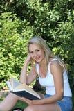 俏丽的微笑的妇女读书在庭院里 免版税库存图片