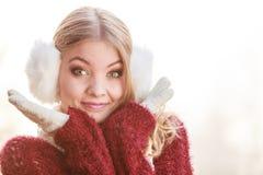 俏丽的微笑的妇女画象白色御寒耳罩的 免版税库存照片