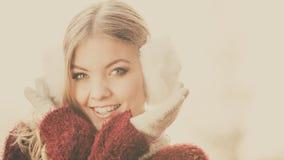 俏丽的微笑的妇女画象白色御寒耳罩的 免版税库存图片
