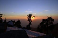 俏丽的日落和五颜六色的天空在雪加盖了小山 免版税库存照片