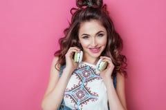 俏丽的时尚凉快微笑的与括号女孩听到在耳机佩带的音乐有卷发的五颜六色的衣裳在桃红色 库存图片