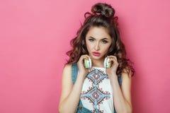 俏丽的时尚凉快的微笑的女孩听到在耳机佩带的音乐有卷发的五颜六色的衣裳在桃红色背景 库存照片