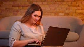 俏丽的正大小模型坐微笑地键入在膝上型计算机的地板是高兴的与在舒适家庭环境的工作 影视素材