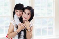俏丽的母亲和她的女儿在家 免版税库存图片
