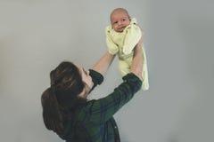 俏丽的母亲提起她的婴孩 图库摄影