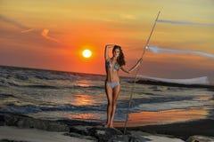 年轻俏丽的比基尼泳装摆在的时尚运动的妇女室外在海滩 免版税库存照片