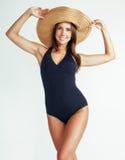 年轻俏丽的深色的在白色背景和泳装隔绝的妇女佩带的夏天帽子准备对假期,微笑 库存图片