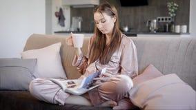 俏丽的深色的女孩在客厅穿丝绸睡衣坐一个沙发晚上,饮用的茶和读 股票录像