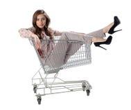 俏丽的深色的妇女和购物台车有购物袋的 免版税库存照片