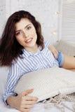 年轻俏丽的深色的妇女在她的坐在窗口,愉快的微笑的生活方式人概念的卧室 免版税图库摄影