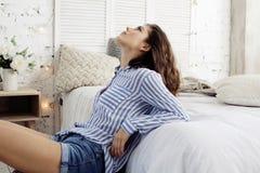 年轻俏丽的深色的妇女在她的坐在窗口,愉快的微笑的生活方式人概念的卧室 库存照片